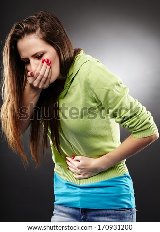 Studio shot of a sick woman about to throw up holding her stomach over gray background - stock photo