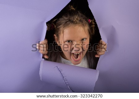 Studio shot of a silly girl with glitter in her hair breaking through purple paper with a crazy look and silly hair. - stock photo