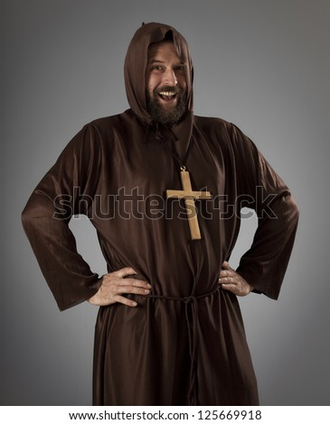 Studio shot of a slightly overweight man wearing a monk robe, laughing while looking at camera.