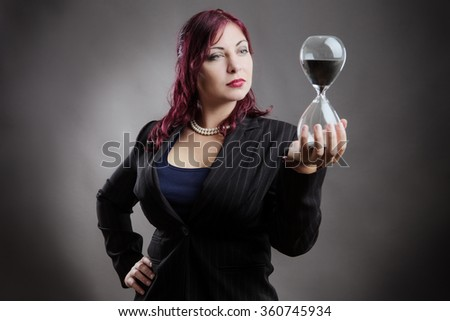 Studio shot of a woman in a suit holding a sand timer in her hands - stock photo