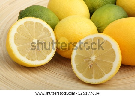 Studio shot of a wooden bowl filled with lemons and limes - stock photo