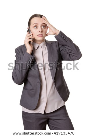 Studio shot of a worried and frustrated looking business woman, who is talking on the phone, using her hand to gesture.