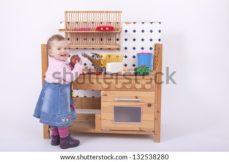 studio shot of a 1 year old baby girl playing in a selfmade wooden kitchen and eating an apple. - stock photo