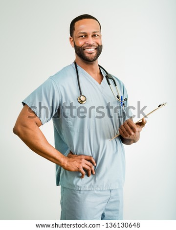 Studio shot of a young African American doctor or nurse holding a clipboard. - stock photo