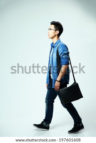 Studio shot of a young asian man walking on gray background - stock photo
