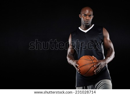 Studio shot of a young basketball player standing with his basketball. African man holsing a basketball against black background with copyspace. - stock photo