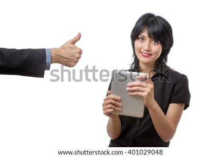 Studio shot of a young beautiful happy business woman using tablet computer with a male colleagues arm in a suit coming into the shot on the lefthand side, showing thumbs up pose. - stock photo