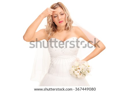 Studio shot of a young bride in a white wedding dress having a headache isolated on white background - stock photo