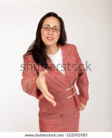 Studio shot of a young businesswoman wearing glasses with an outstretched hand