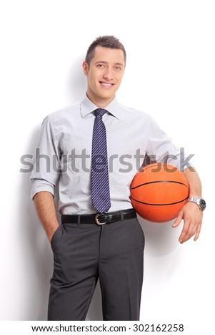 Studio shot of a young cheerful businessman holding a basketball and looking at the camera isolated on white background - stock photo