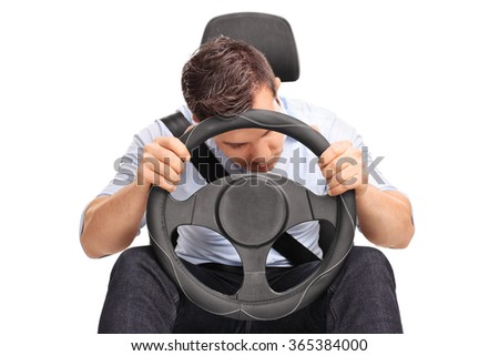 Studio shot of a young driver sleeping while driving isolated on white background - stock photo