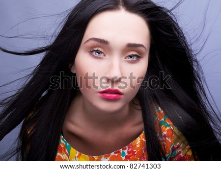 Studio shot of a young ethnic brunette beauty wearing luxury bright dress. - stock photo