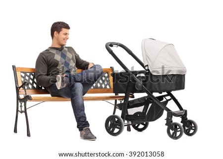 Studio shot of a young father sitting on a bench with a baby stroller beside him isolated on white background