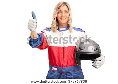 Studio shot of a young female car racer holding a helmet and giving a thumb up isolated on white background