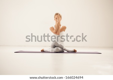 Studio shot of a young fit woman doing yoga exercises. - stock photo