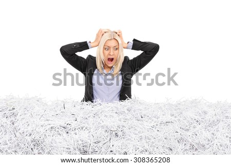 Studio shot of a young furious businesswoman stuck in a pile of shredded paper isolated on white background - stock photo