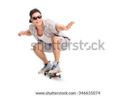 Studio shot of a young joyful skater riding a skateboard isolated on white background - stock photo