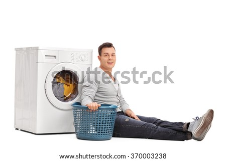 Studio shot of a young man sitting by a washing machine and doing laundry isolated on white background - stock photo