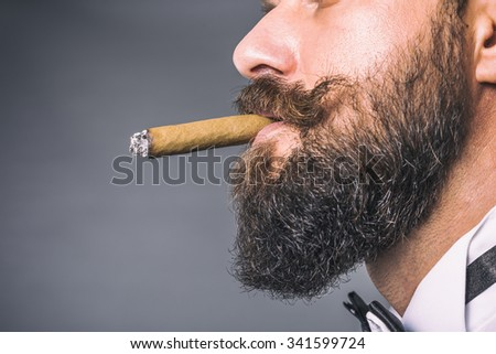 Studio shot of a young man with beard and mustache smoking a cigar over gray background