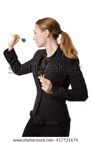Studio shot of a young, pretty business woman, wearing a suit, aiming a dart, ready to throw.   - stock photo
