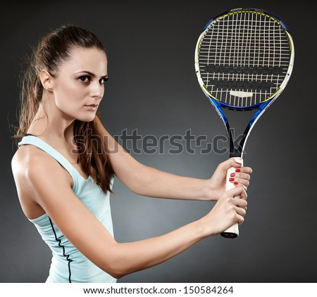 Studio shot of a young woman executing a backhand volley - stock photo