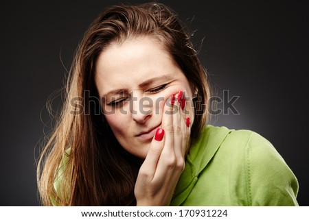 Studio shot of a young woman having a severe tooth ache with hand on cheek over grey background - stock photo
