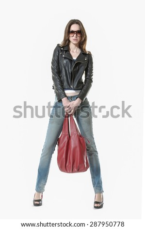 Studio shot of a young woman in jeans with bag in studio - stock photo