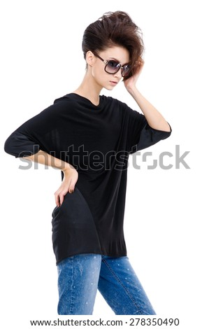 Studio shot of a young woman in jeans with sunglasses  - stock photo