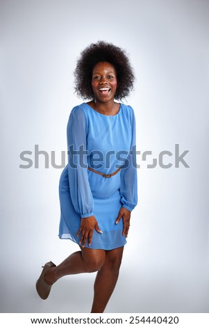 Studio shot of african woman in blue dress laughing on white background - stock photo
