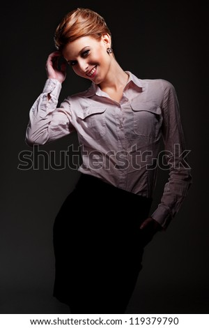 studio shot of alluring woman posing over dark background - stock photo