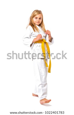 Studio shot of an adorable girl in kimono training martial art over white background
