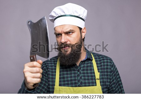 Studio shot of an angry bearded man holding a butcher knife over gray background