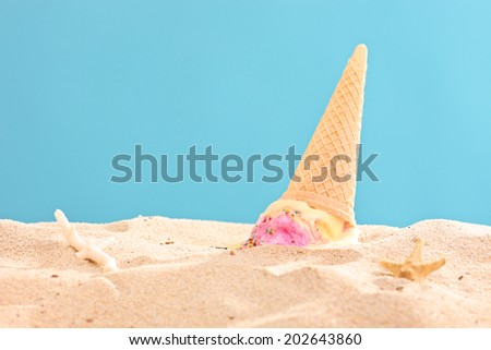 Studio shot of an ice cream splashed on sand on blue background - stock photo