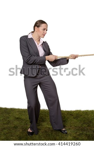 Studio shot of an office business worker standing on grass, pulling on a large rope in a tug of war.  Isolated on white