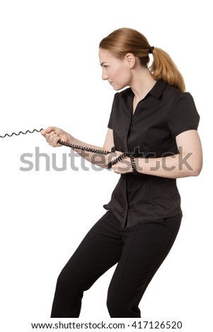 Studio shot of an office business worker standing on grass, pulling on a telephone wire in a tug of war.  Isolated on white