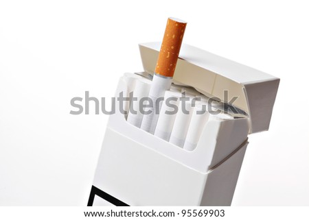 Studio shot of an opened pack of cigarettes, with a different cigarette popping out - stock photo