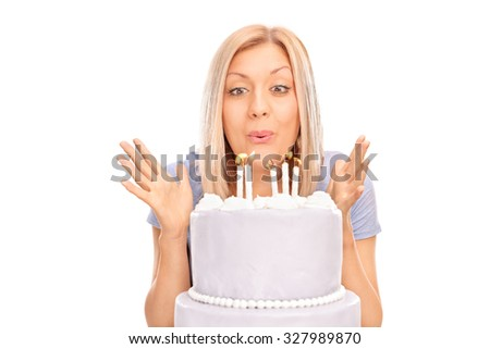 Studio shot of an overjoyed blond woman blowing candles on a birthday cake isolated on white background - stock photo