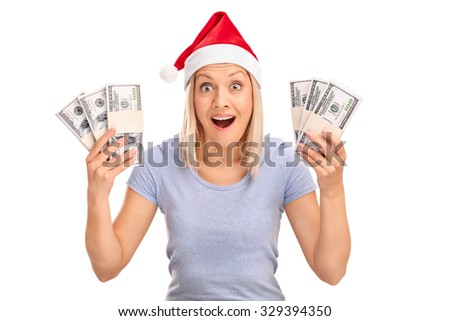 Studio shot of an overjoyed woman with Santa hat holding a few stacks of money isolated on white background - stock photo