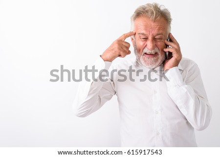 Studio shot of angry senior bearded man thinking while talking on mobile phone against white background