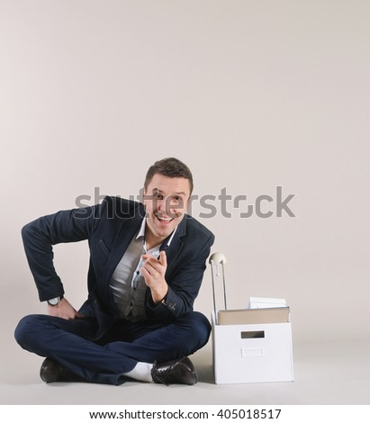 studio shot of attractive positive man with office stuff in the box sitting on the floor in suit on grey background; business concept