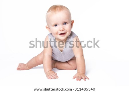 Studio shot of baby boy playing on the floor looking at the camera.
