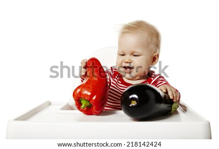 Studio shot of baby is choosing vegetables. - stock photo
