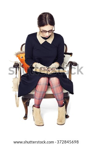 Studio shot of beautiful girl sitting on armchair and reading a book. - stock photo