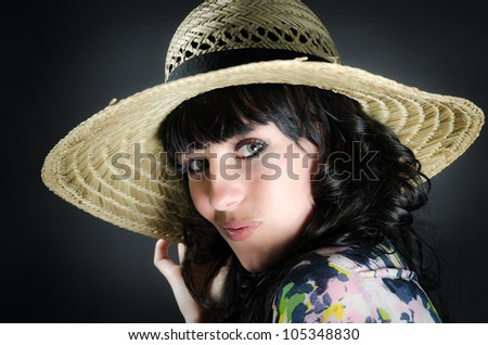 Studio shot of beautiful woman with straw hat on black background - stock photo