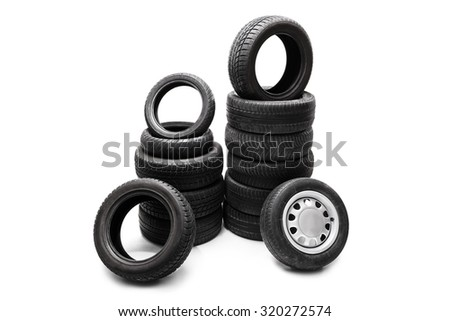 Studio shot of  black car tires piled up in two separate stacks isolated on white background - stock photo