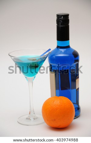 Studio shot of blue martini cocktail with olive, bottle of blue curacao liqueur, and orange fruit. - stock photo