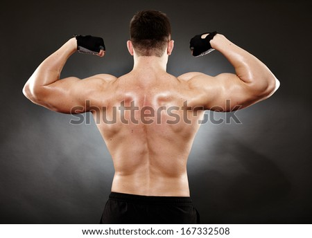 Studio shot of bodybuilder showing his back muscles - stock photo