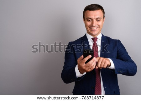 Studio shot of businessman wearing suit while using mobile phone against gray background