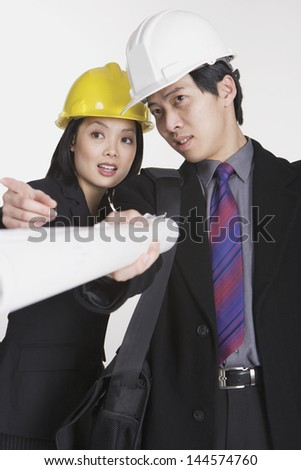 Studio shot of businesspeople wearing hard hats