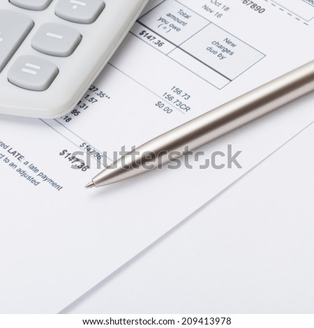 Studio shot of calculator and pen over some receipt - 1 to 1 ratio